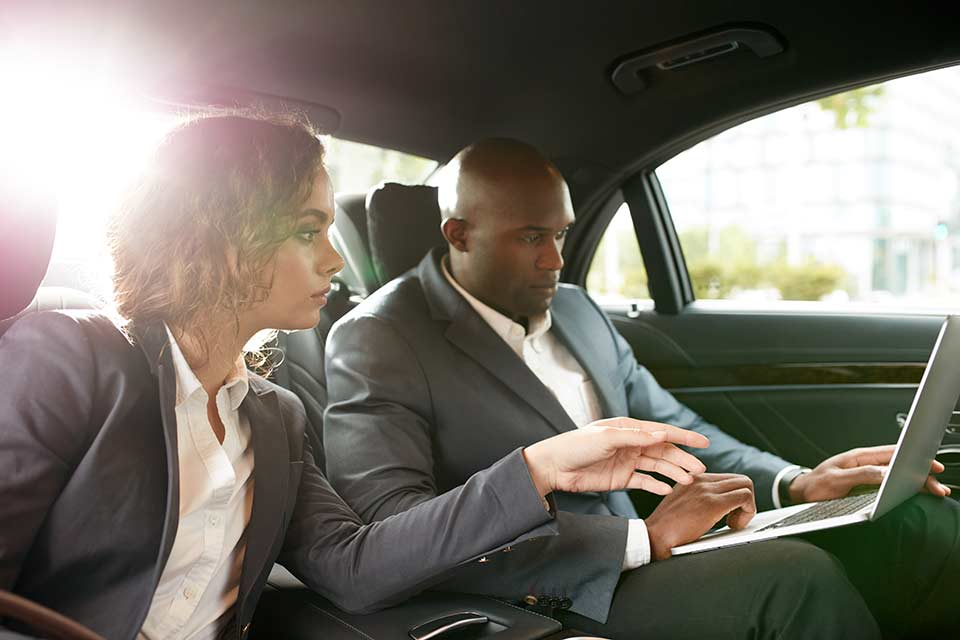 African/American man and white woman conducting business in limousine