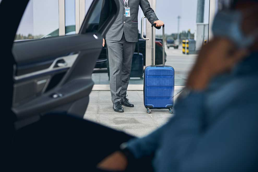 Chauffeur bringing suitcase to car for Airport services