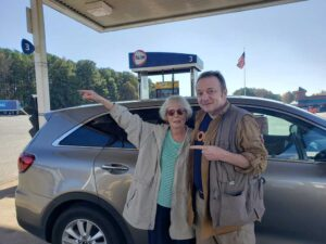 Couple in front of car at a gas station pointing to the road